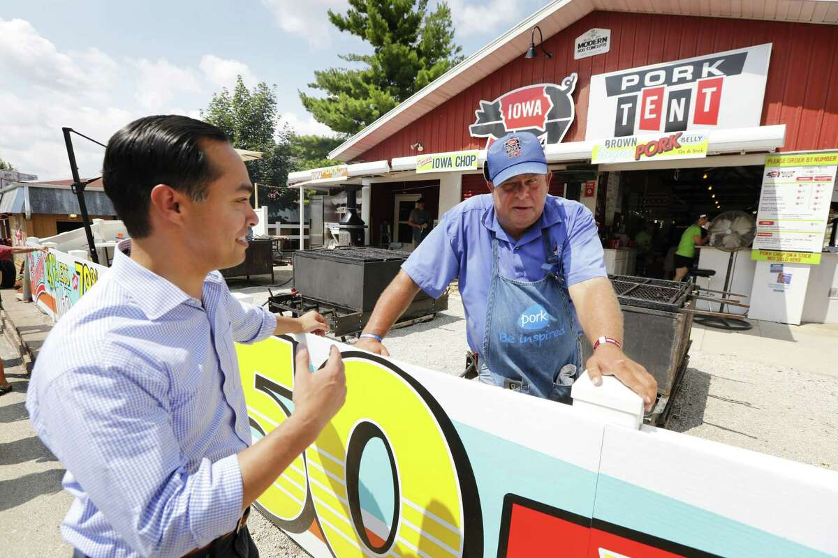 Former Housing and Urban Development Secretary Julian Castro talks with Iowa Pork Producers tent worker Dana Wanken, right, during a visit to the Iowa State Fair, Friday, Aug. 17, 2018, in Des Moines, Iowa. (AP Photo/Charlie Neibergall)