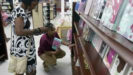 Former New Orleans resident Angela Williams, right, helps a customer Tuesday, Aug. 14, 2018, in Abba Father's Christian Store, one of the two she owns. She still bears bad memories of driving from New Orleans with her family as the Category 5 Katrina hurricane slammed into the northern Gulf Coast and upended her life. After additional setbacks, she credits her faith for her present status and prosperous life in San Antonio.