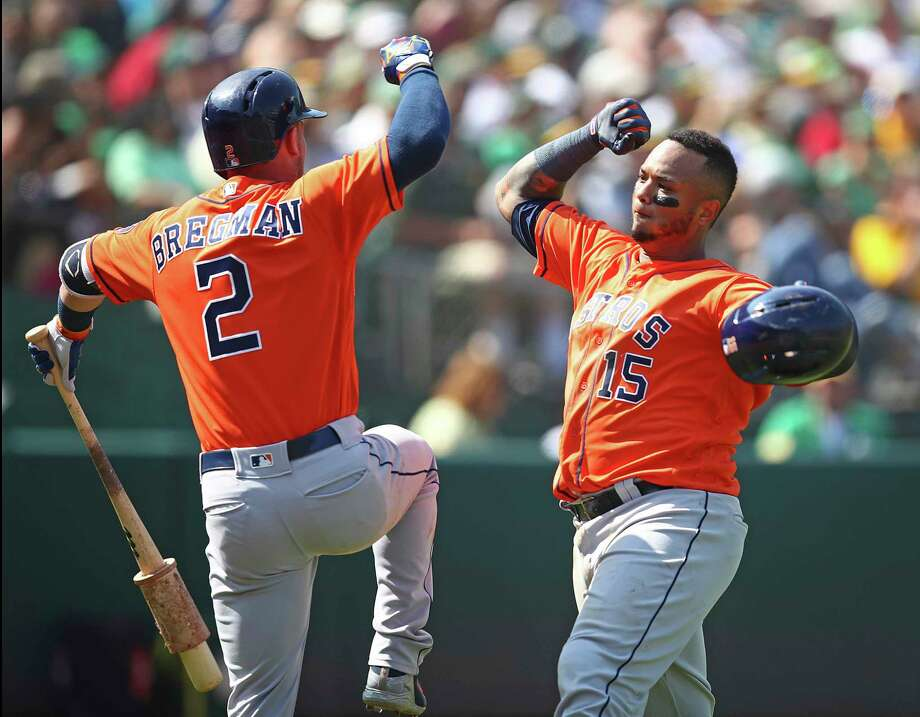 Houston Astros' Martin Maldonado, right, celebrates with Alex Bregman (2) after hitting a home run off Oakland Athletics' Emilio Pagan in the seventh inning of a baseball game Sunday, Aug. 19, 2018, in Oakland, Calif. (AP Photo/Ben Margot) Photo: Ben Margot, Associated Press / Copyright 2018 The Associated Press. All rights reserved.