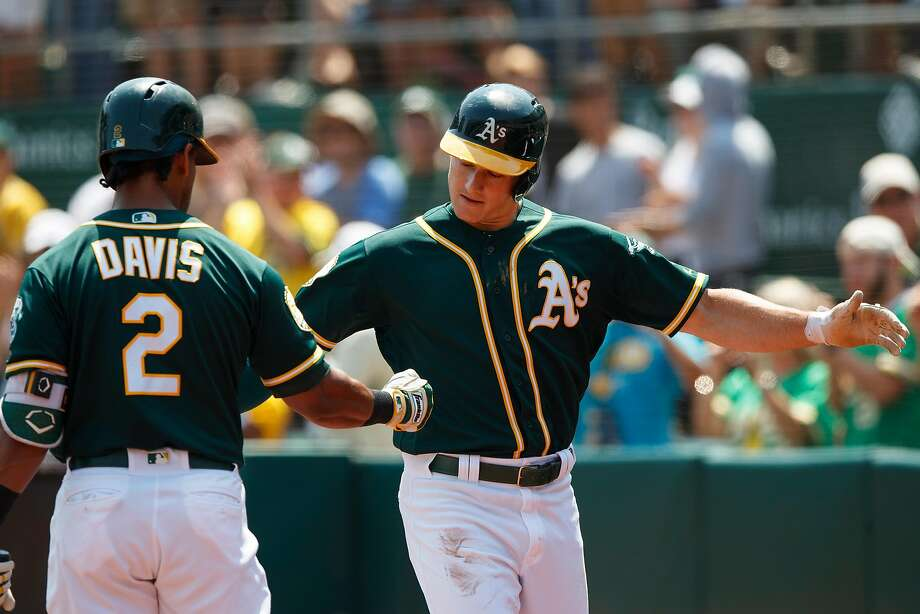 OAKLAND, CA - AUGUST 19:  Matt Chapman #26 of the Oakland Athletics is congratulated by Khris Davis #2 after hitting a home run against the Houston Astros during the first inning at the Oakland Coliseum on August 19, 2018 in Oakland, California. (Photo by Jason O. Watson/Getty Images) Photo: Jason O. Watson / Getty Images