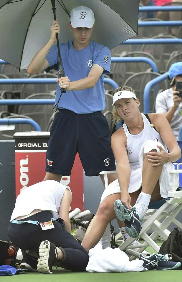 CoCo Vandeweghe has a trainer look at an injury on her right leg during the third set against Magdalena Rybarikova on Sunday at the Connecticut Open. Photo: Peter Hvizdak / Hearst Connecticut Media / New Haven Register
