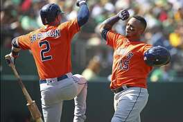 Houston Astros' Martin Maldonado, right, celebrates with Alex Bregman (2) after hitting a home run off Oakland Athletics' Emilio Pagan in the seventh inning of a baseball game Sunday, Aug. 19, 2018, in Oakland, Calif. (AP Photo/Ben Margot)