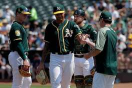 PItcher Sean Manaea (55) gives the ball to manager Bob Melvin in the fifth inning as the Oakland Athletics played the Houston Rockets at the Coliseum in Oakland, Calif., on Sunday, August 19, 2018.