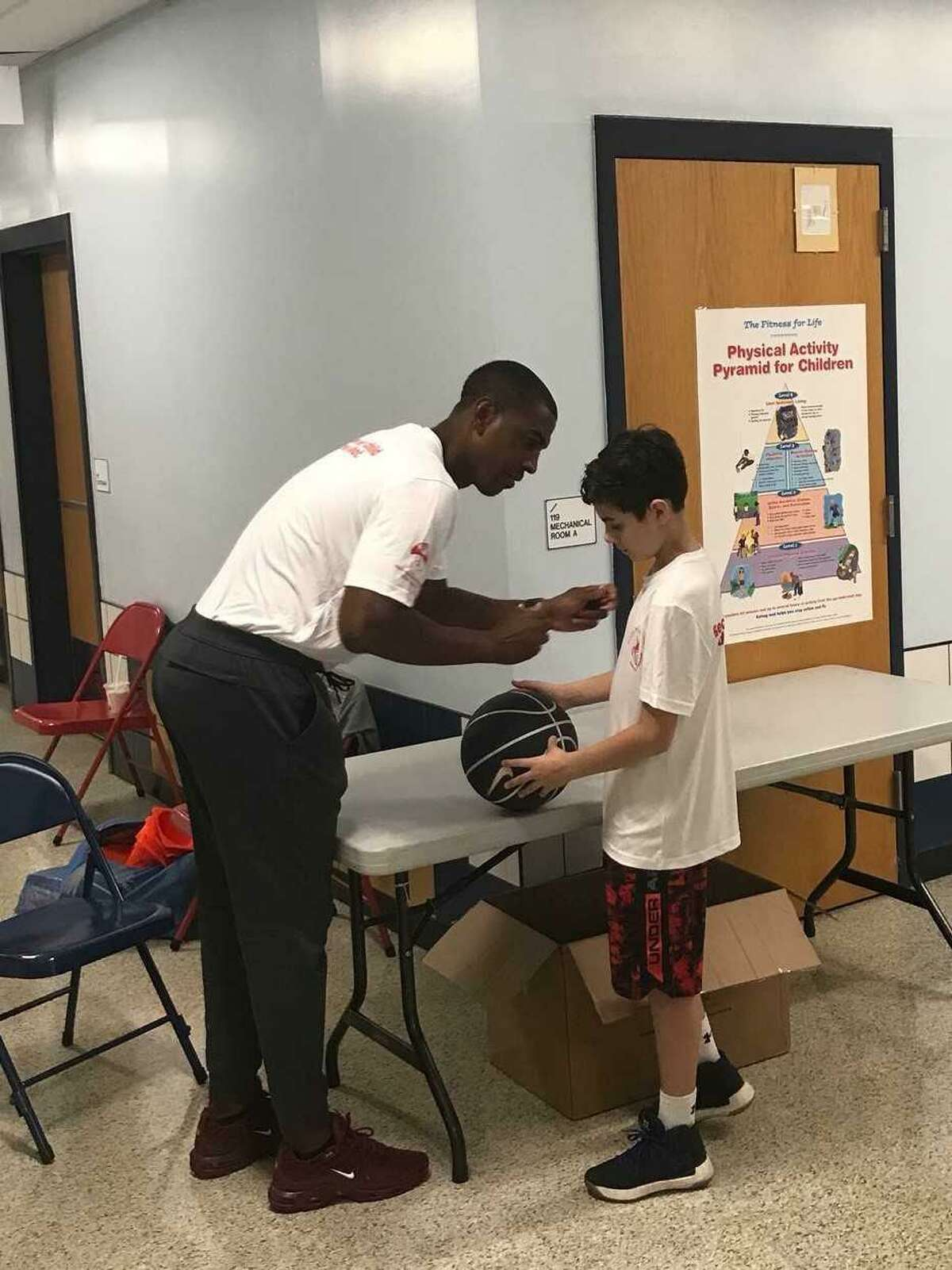 Former UConn coach Kevin Ollie signs an autograph during a charity event in Gales Ferry. (Jeff Jacobs/Hearst Connecticut Media Group )