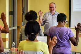 Instructor Daniel McCall simulates the swearing in process for immigrants seeking citizenship during classes to help them with the process on August, 11, 2018 in Gaithersburg, Md.