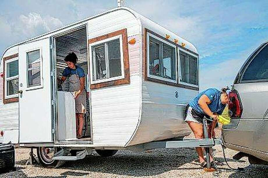 Kami Stahl secures the trailer before unhooking from the vehicle as partner Mikaela Endress prepares for opening inside the trailer that is their mobile ice cream business. Kamaela's Creamery is a mobile ice cream business Endress opened with Stahl in May that travels to events and locations around central Illinois. Photo:       David Zalaznik | Journal Star (AP)