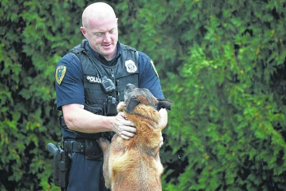 Patrolman Scott Cleveland greets police dog Bo after a game of fetch. Photo:       Nick Draper | Journal-Courier