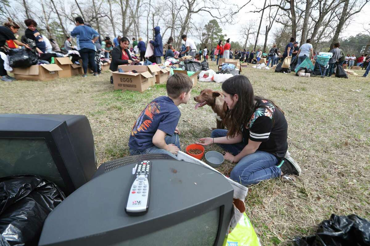 Volunteers Jordon Brock, 12, (left) and Halle Ludwig give a stray dog food and water as Hurricane Harvey victims receive help Sunday, Feb. 18, 2018, in Houston.