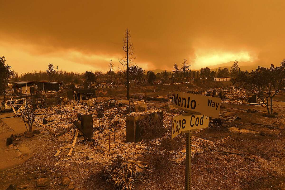 FILE - In this Friday, July 27, 2018, file photo, homes leveled by the Carr Fire line the Lake Keswick Estates area of Redding, Calif. California lawmakers are abandoning a controversial proposal by Gov. Jerry Brown to shield electrical utilities from some financial liability for wildfires. (AP Photo/Noah Berger, File)