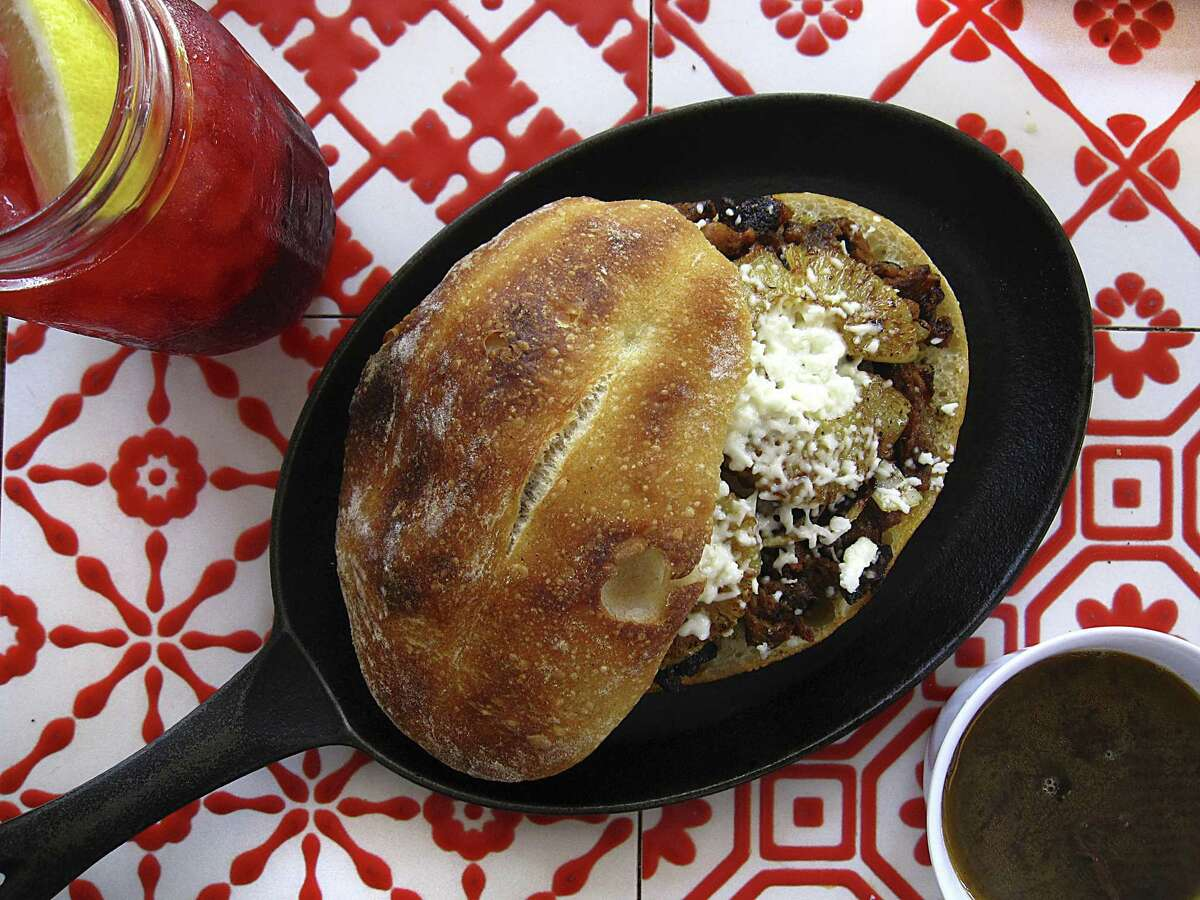 A torta with pork al pastor, pineapple and queso fresco on telera bread, along with a jamaica agua fresca and a side of black bean soup from La Panadería, which is planning to open a third location at the Rim shopping center next summer.