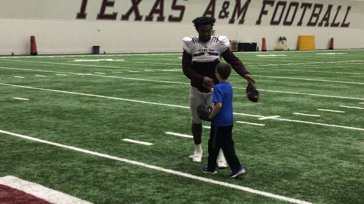 Texas A&M linebacker Tyrel Dodson takes time to play catch with Will Zwerneman, 9, after Friday's practice in College Station.