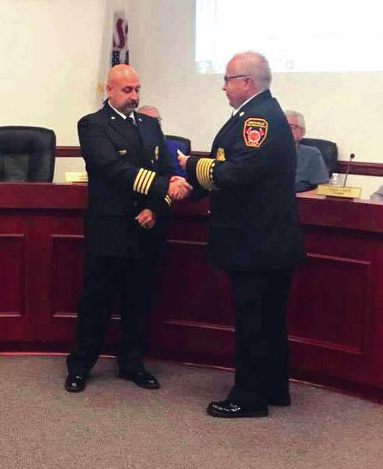Maryville Fire Chief Kevin Flaugher, right, presents George May with his Deputy Fire Chief badge at the last regular meeting of the Maryville Board of Trustees . May was appointed to serve as the full-time Deputy Chief of the Maryville Fire Department. Photo:       John Sommerhof/Intelligencer