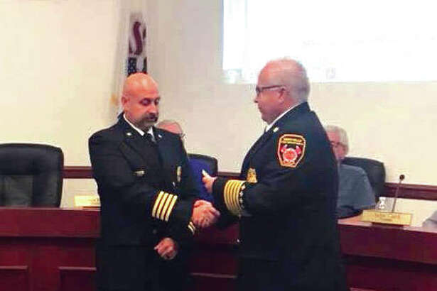 Maryville Fire Chief Kevin Flaugher, right, presents George May with his Deputy Fire Chief badge at the last regular meeting of the Maryville Board of Trustees . May was appointed to serve as the full-time Deputy Chief of the Maryville Fire Department.