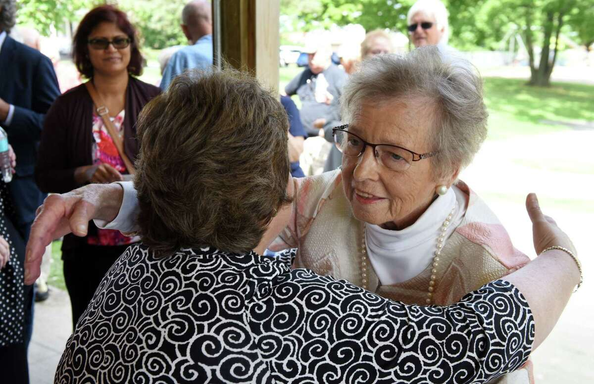 Karen Johnson, right, is embraced by Mona Golub after being presented with the Patroon Award by Mayor Gary McCarthy on Monday, Aug. 20, 2018, at Steinmetz Park in Schenectady, N.Y. The Patroon Award is the highest honor the City of Schenectady can bestow upon its residents. (Will Waldron/Times Union)