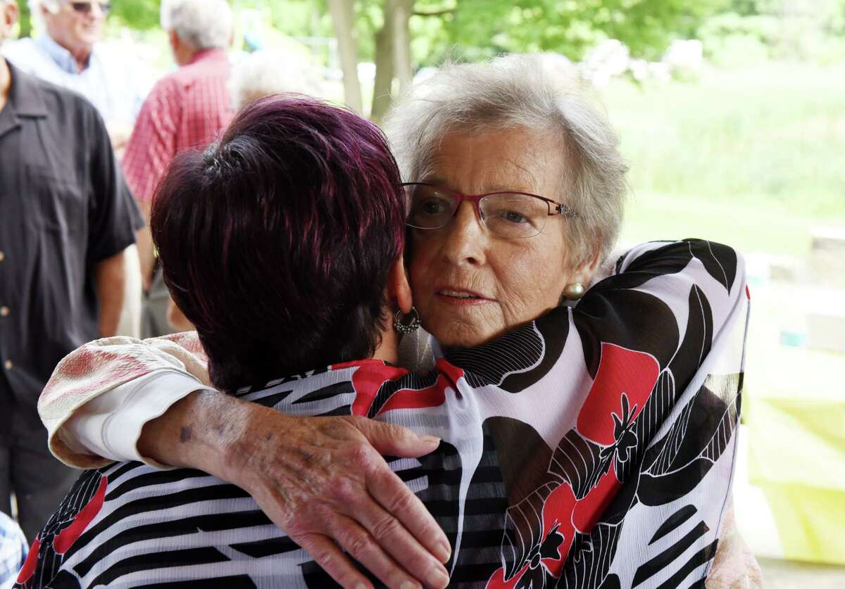 Karen Johnson, right, is embraced by Schenectady Councilwoman Leesa Perazzo, left, after being presented with the Patroon Award on Monday, Aug. 20, 2018, at Steinmetz Park in Schenectady, N.Y. The Patroon Award is the highest honor the City of Schenectady can bestow upon its residents. (Will Waldron/Times Union)