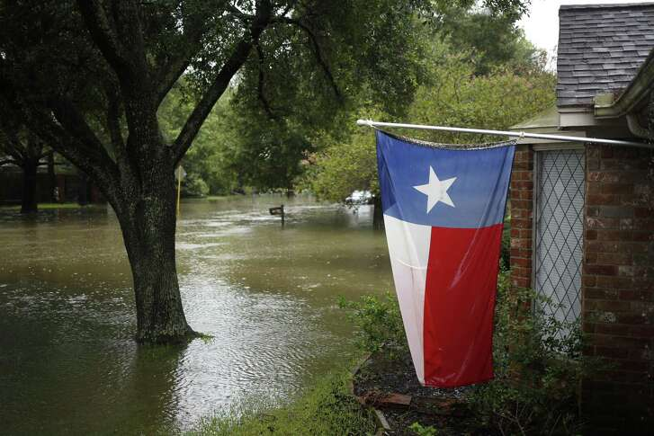 A Texas State flag hangs from a home surrounded by floodwaters from Hurricane Harvey in The Woodlands on Tuesday, Aug. 29, 2017. Photographer: Luke Sharrett/Bloomberg