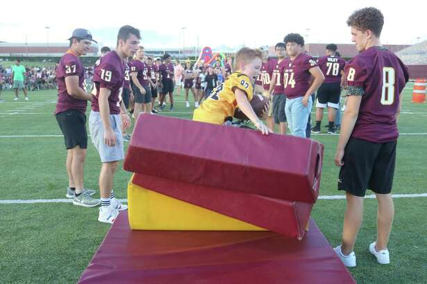 Diving into a stack of blocking pads proved popular for the kids during the Kickoff Party Saturday night.