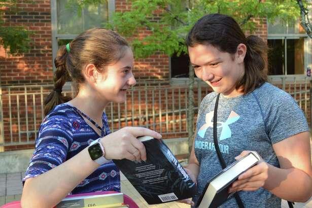 Friends Alexis Pensiero,13, left, and Ervina Ujkaj, 13, of Darien talk about books at the Summer Reading Teen Finale celebration at Darien Library, Thursday, Aug. 16, 2018, in Darien, Conn.