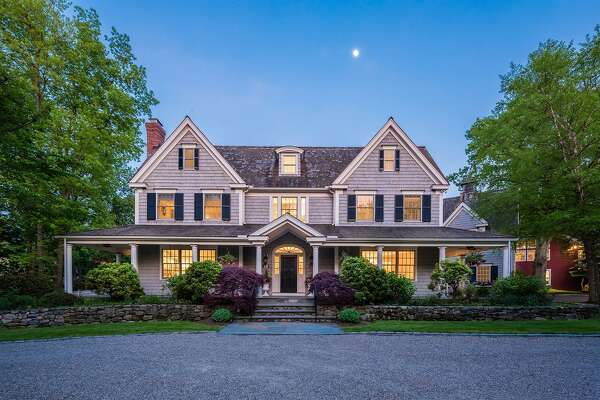 The gray colonial house at 369 Sasco Hill Road features 11 rooms, a carriage house, a covered wrap-around front porch, and a wealth of entertainment features in the backyard.