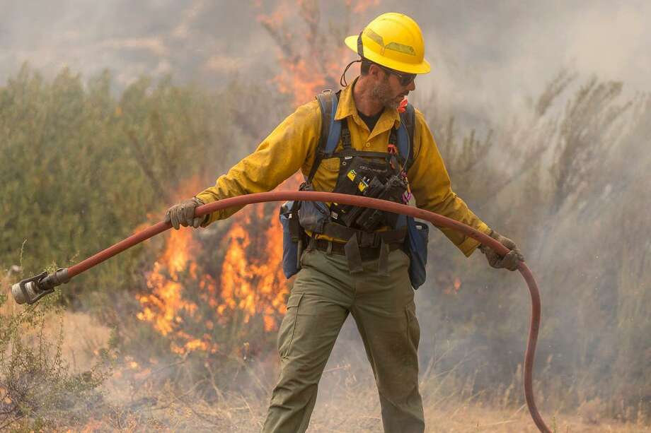 A wildland firefighter pulls a hose at the Cougar Creek Fire in the Entiat River Valley, south of Lake Chelan, in Central Washington, August 2018. Photo: INCIWEB