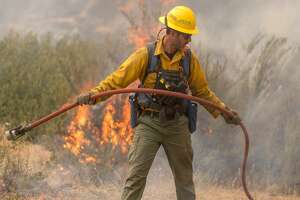 A wildland firefighter pulls a hose at the Cougar Creek Fire in the Entiat River Valley, south of Lake Chelan, in Central Washington.