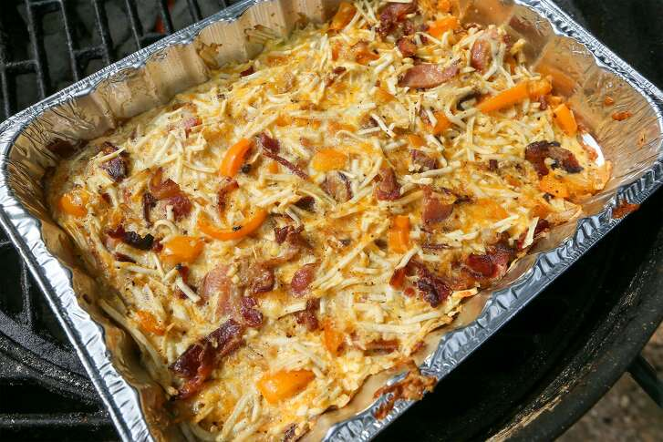 An outdoor breakfast casserole consisting of hash brown potatoes, bacon, eggs, bell pepper, yellow onion, minced garlic, shredded cheddar cheese and kosher salt on the grill at Chuck's Food Shack.