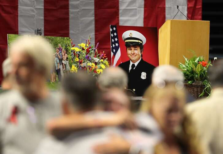 WEST VALLEY CITY, UT - AUGUST 20: A  picture of Battalion Chief Matthew David Burchett, sits on stage as mourners hug each other before his funeral at the Maverik Center on August 20, 2018 in West Valley City, Utah. Burchett was killed on August 13, 2018 as he was fighting the Mendocino Complex Fire in Northern California, the largest fire in California history. Burchett was one of several Utah firefighters that were sent to California to help out with several large fires. Burchett is survived by his wife and a seven year old son. (Photo by George Frey/Getty Images)