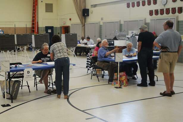 Voters check in at the polls for the Democratic and Republican primaries at Orange Avenue School in Milford on Tuesday.