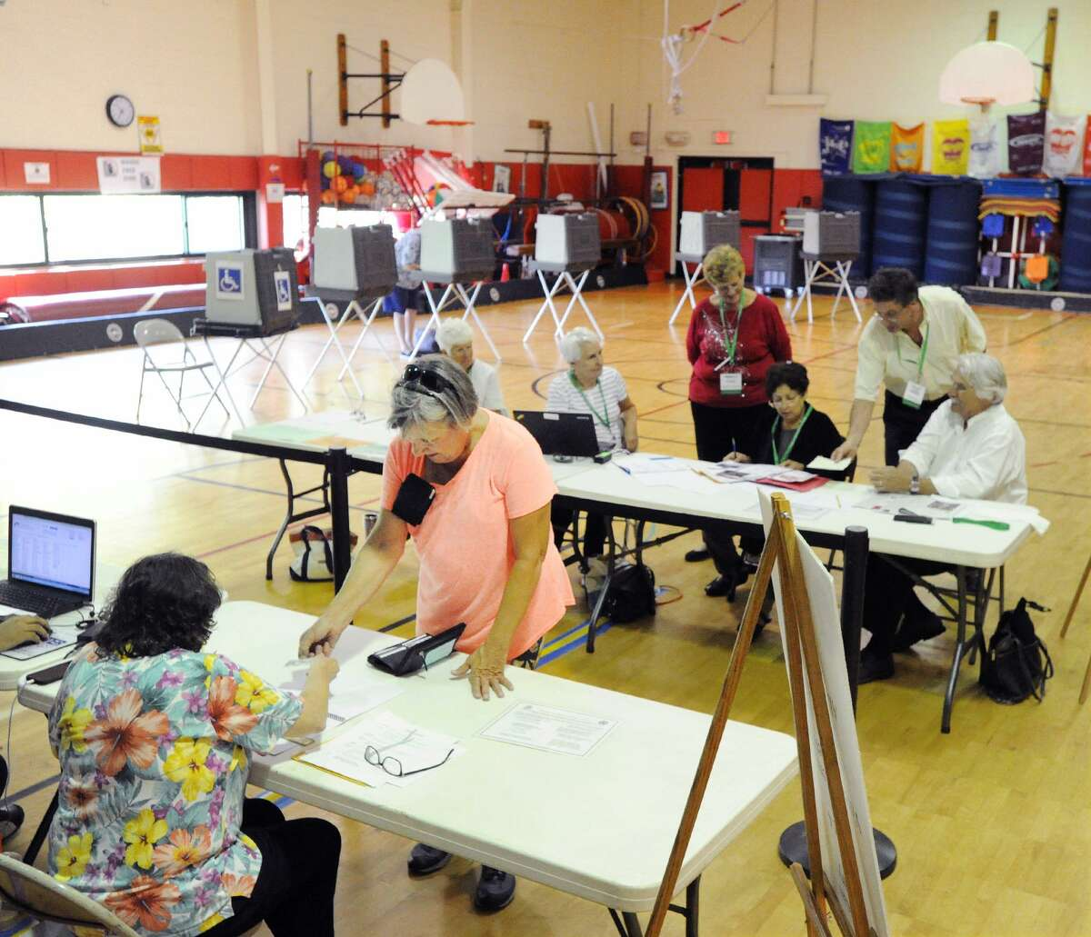 Ann Riley of Greenwich, bottom left, shows her identification before voting during the state primary elections at the New Lebanon School in Greenwich.