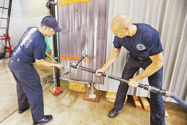 "Alton Fire Department Capt. Rick Newman, right, holds the department's new ""piercing nozzle"" as firefighter Jacob Iman, left, prepares to hammer it through a piece of sheet metal during an operational demonstration Monday. The nozzle is used to access areas via ceilings, roofs or even car hoods when needed, and can help protect firefighters in certain situations. The nozzle was paid for with a grant from Illinois American Water as part of the company's ongoing support of local fire departments."