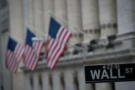 """In this file photo taken on February 16, 2017 a street sign is seen near the New York Stock Exchange in New York. Bolstered by a period of extraordinary monetary stimulus followed by generous tax cuts, Wall Street stands at the cusp of another landmark this week. The US stock market on August 22, 2018 will mark 3,453 straight days without suffering a drop of 20 percent. That makes it the longest """"bull market"""" since World War II, according to leading Wall Street statisticians."""