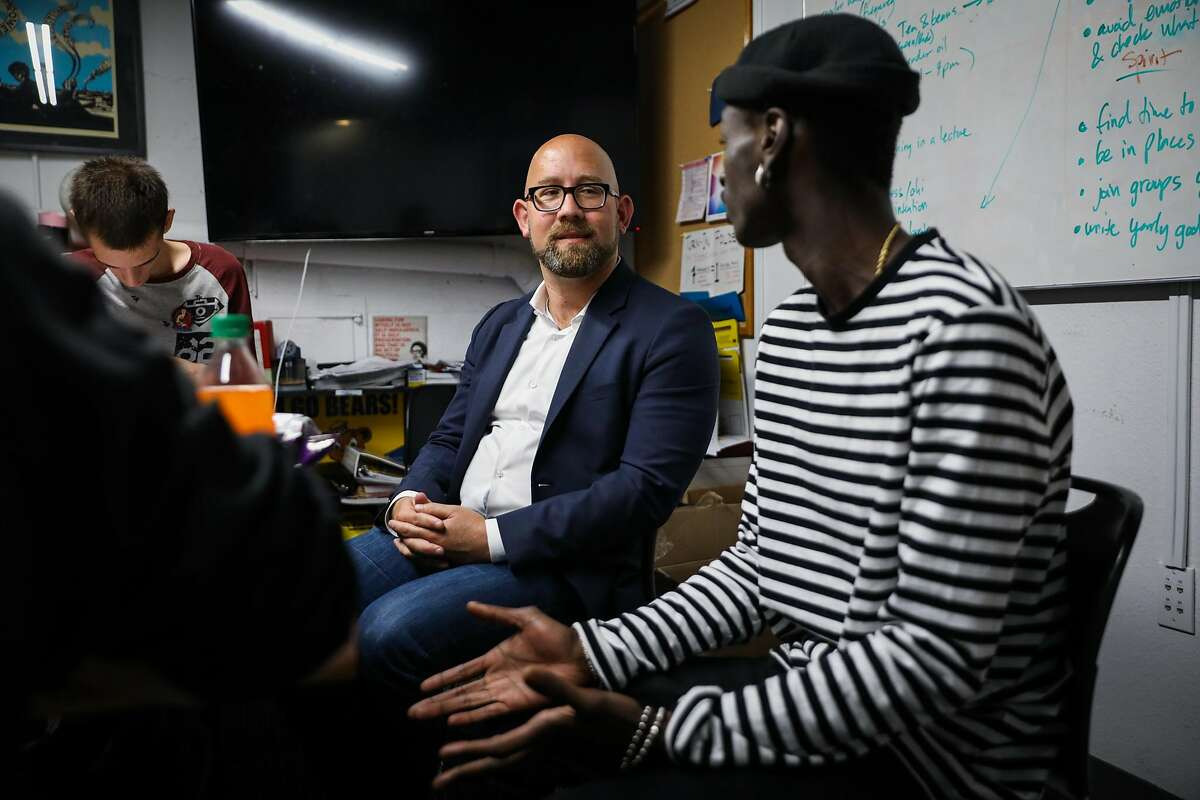 Supervisor Rafael Mandelman (left) converses with client Richard Reavson, 23, (right) during a tour of the Larkin Street Youth Services in San Francisco, California, on Thursday, Aug. 16, 2018.