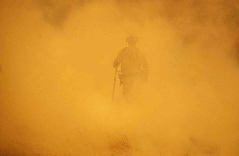 A firefighter walks through smoke during the Mendocino Complex fire in Lakeport, California, on July 30, 2018.  The Mendocino Complex -- made up of two fires --  has burned more than 24,000 acres in total since July 27. Thousands of firefighters in California made some progress against several large-scale blazes that have turned close to 200,000 acres (80,940 hectares) into an ashen wasteland, destroyed expensive homes, and killed eight fire personnel and civilians in the most populous US state.  Photo: Josh Edelson / AFP / Getty Images