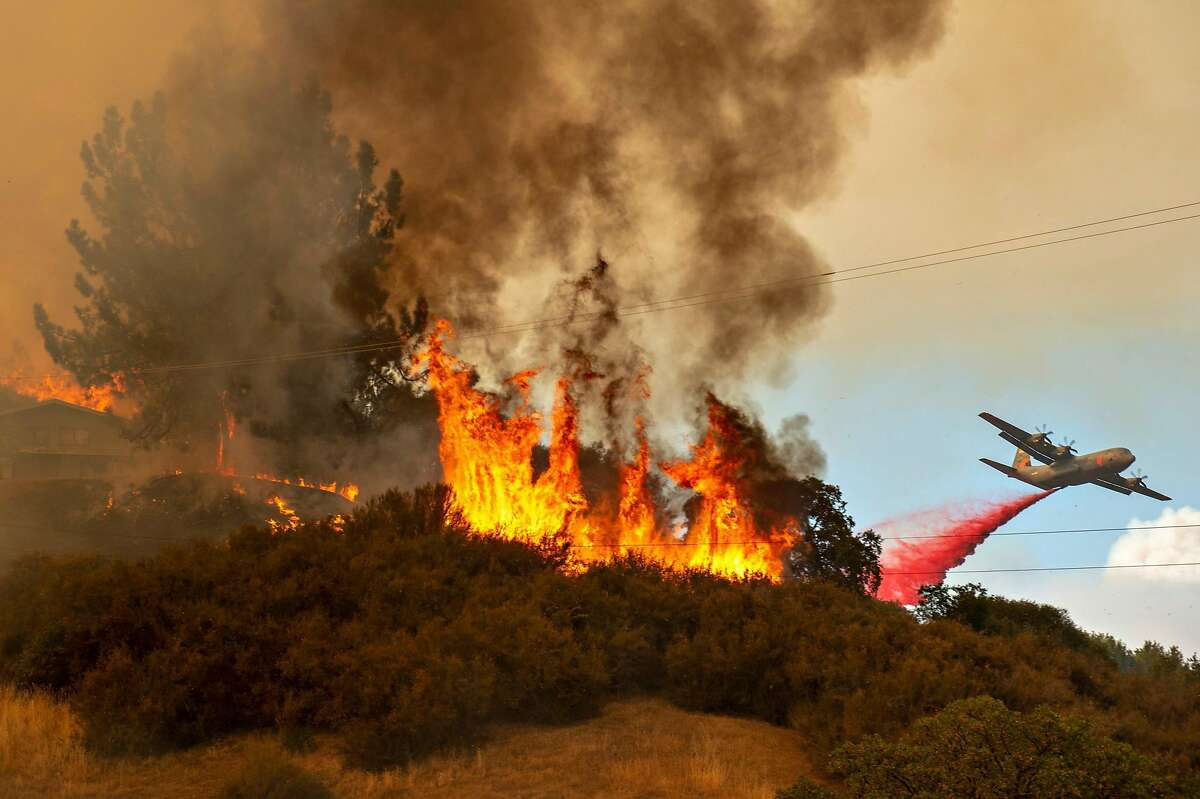 Fire retardant is dropped near a home as the Mendocino Complex Fire burns off of Keck Road, just west of Lakeport, Calif., on Monday, July 30, 2018. (Jose Luis Villegas/Sacramento Bee/TNS)