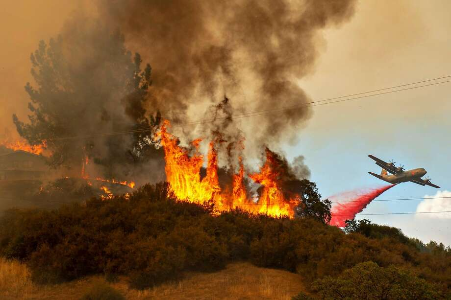 Fire retardant is dropped near a home as the Mendocino Complex Fire burns off of Keck Road, just west of Lakeport, Calif., on Monday, July 30, 2018. (Jose Luis Villegas/Sacramento Bee/TNS) Photo: Jose Luis Villegas / Sacramento Bee