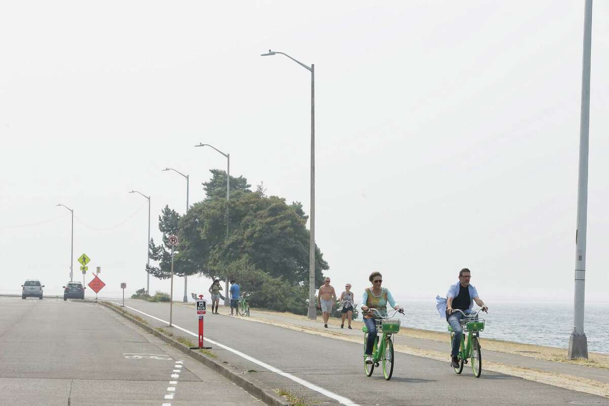 People brave the smoke-filled conditions on Alki Beach in West Seattle as wildfire haze continues to cloud the city, Monday, Aug. 20, 2018.