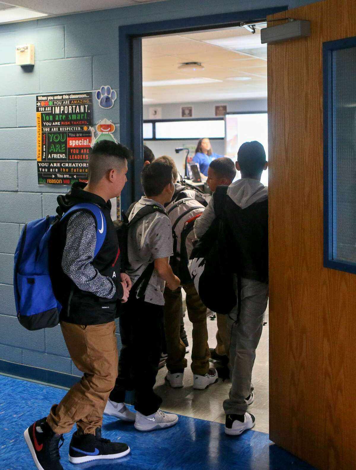 Students enter Ashley Barrera's 6th-grade Advanced STEM Science class at Dwight Middle School on the first day of school on Monday, Aug. 20, 2018. Hundreds of students, about half of all South San incoming sixth graders, have enrolled in the middle school academies, which will allow students to specialize in STEM, health science or fine arts and challenge them with advanced coursework.