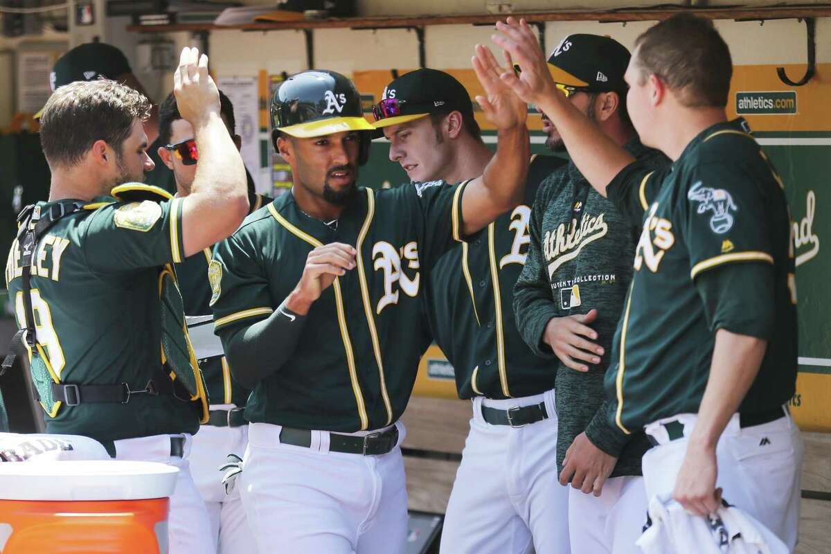 Oakland Athletics shortstop Marcus Semien (10) is greeted by teammates back at the dugout after scoring on a line drive by A's Khris Davis (2) during the first inning of an MLB game between the Oakland Athletics and Houston Astros at the Oakland-Alameda County Coliseum on Saturday, Aug. 18, 2018, in Oakland, Calif.