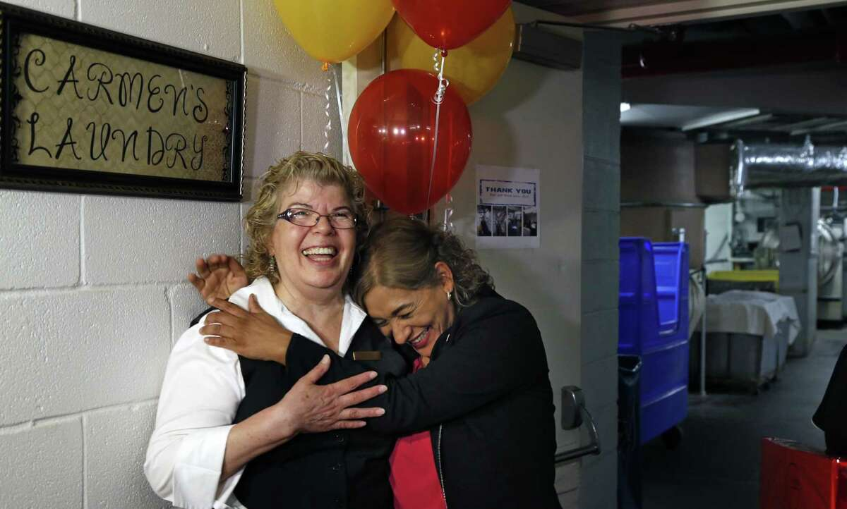 """Rebecca Leal, hugs Carmen Alvarado after they had hung up a sign renaming the Laundry in her honor. The St. Anthony Hotel will surprise Carmen Alvarado with a celebration to mark her 45th year of working in the hotel's laundry room, which will be renamed """"Carmen's Laundry."""" Photos taken on Monday, Aug.20, 2018."""