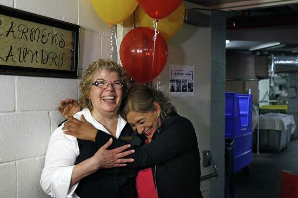 "Rebecca Leal, hugs Carmen Alvarado after they had hung up a sign renaming the Laundry in her honor. The St. Anthony Hotel will surprise Carmen Alvarado with a celebration to mark her 45th year of working in the hotel's laundry room, which will be renamed ""Carmen's Laundry."" Photos taken on Monday, Aug.20, 2018."