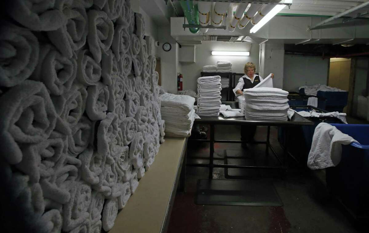 """After celebration Carmen Alvarado folds towels. The St. Anthony Hotel will surprise Carmen Alvarado with a celebration to mark her 45th year of working in the hotel's laundry room, which will be renamed """"Carmen's Laundry."""" Photos taken on Monday, Aug.20, 2018."""