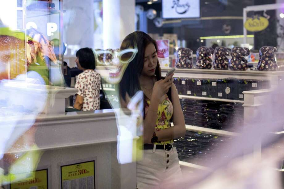 A customer looks at a smartphone in a shopping center in Bangkok, Thailand, on Saturday June 16, 2018. By 2020, more than half of the world's population