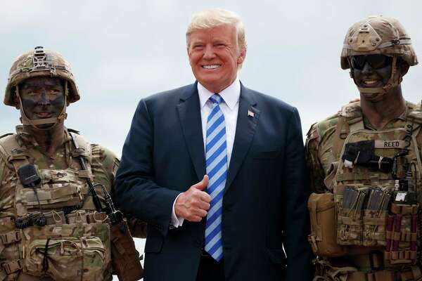 "President Donald Trump poses for a photo with participants of an air assault exercise at Fort Drum, N.Y., Monday, Aug. 13, 2018, before a signing ceremony for H.R. 5515, the ""John S. McCain National Defense Authorization Act for Fiscal Year 2019."" (AP Photo/Carolyn Kaster)"