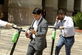 Chairman Rey Saldaña (left) parks his scooter near the Bexar County Courthouse on Aug. 15, 2018. City staff presented a set of recommendations Monday to the City Council's Transportation Committee, including a proposal that electric scooters follow the same laws as bicycles, including staying off sidewalks, but Saldaña said that's a no-go for him.
