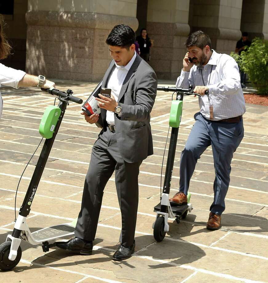 Rey Saldana,L, parks his scooter near the Courthouse on Aug. 15. City staff presented a set of recommendations Monday to the City Council's Transportation Committee, including a proposal that electric scooters follow the same laws as bicycles. That includes staying off sidwalks. Photo: Ronald Cortes / / 2018 Ronald Cortes