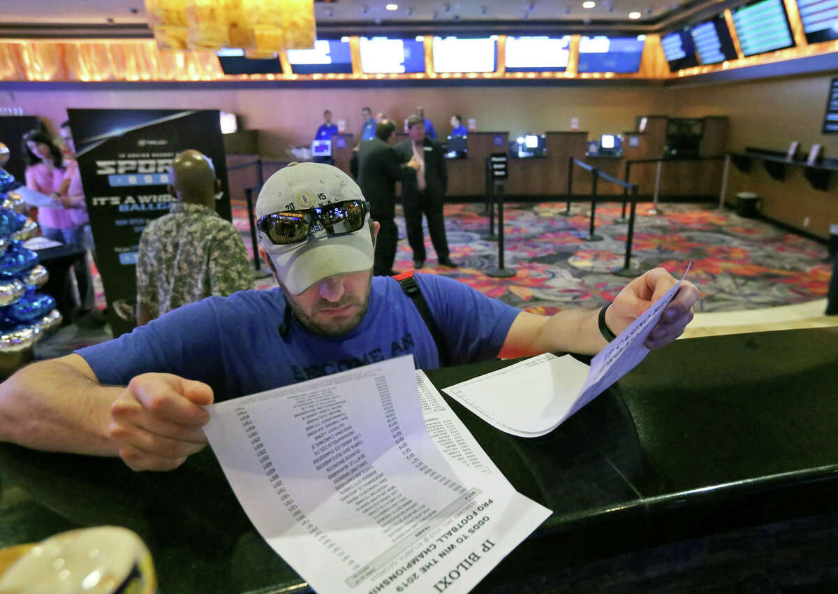 FILE - In this Aug. 3, 2018, file photo, Marvin Werkley, of Mobile, Ala., looks over the wager sheets at the IP Casino Resort & Spa in Biloxi, Miss., before making a bet. Colleges are looking for a way to get a piece of the action from legal sports wagering. Schools in states where legal wagering has started or soon will are considering joining professional sports leagues in pursuing legislation requiring sports book operators to pay them a percentage of the amount wagered on their games. (John Fitzhugh/The Sun Herald via AP, File)