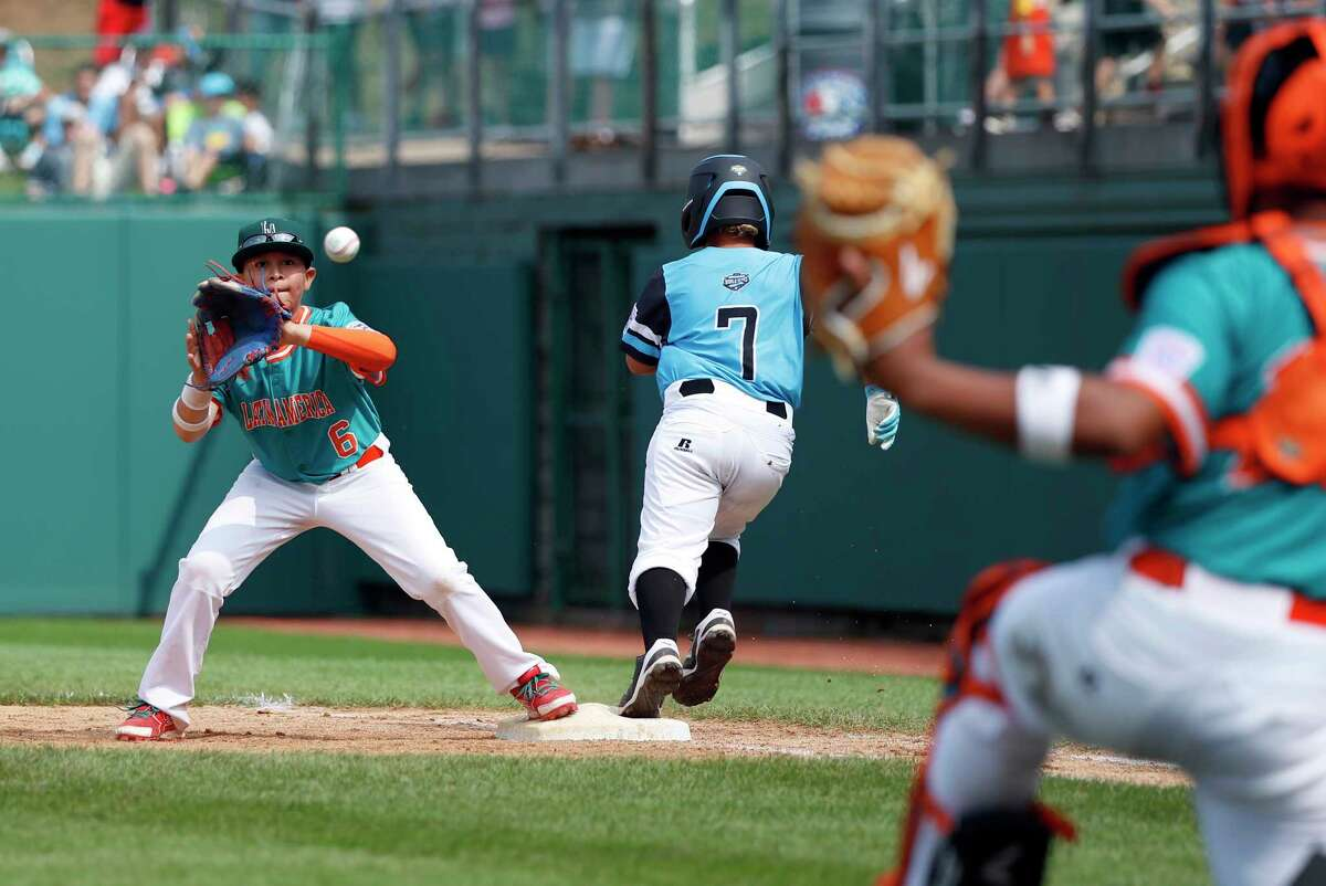 Puerto Rico's second baseman Gabriel Rivera (6) stretches for the throw from catcher Adan Sanchez covering first base as Puerto Rico's Devin Ortiz (7) reaches safely on a bunt in the fifth inning of an elimination baseball game at the Little League World Series tournament in South Williamsport, Pa., Monday, Aug. 20, 2018. Puerto Rico won the game 3-1 eliminating Panama. (AP Photo/Tom E. Puskar)