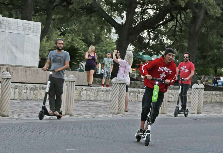 Scooters riders cross Alamo Street last summer. A half-dozen firms will have almost 6,500 dockless vehicles on San Antonio streets once the ride share giant Lyft deploys its first 250 of them here. Photo: Ronald Cortes / / 2018 Ronald Cortes