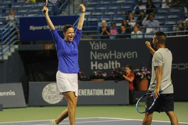 Lindsay Davenport celebrates with her mixed doubles partner, Yale tennis team member Michael Sun, 18, of Livingston, NJ, after a winning point in their match with James Blake and Yale partner Caroline Dunleavy, of Darien, at the Connecticut Open tennis tournament in New Haven, Conn. on Monday, August 20, 2018.
