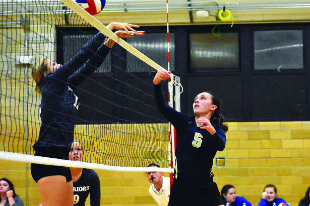 Father McGivney's Claire McKee, right, punches a ball past a blocker during the second game against Hardin Calhoun in the third match of the Roxana Tournament.